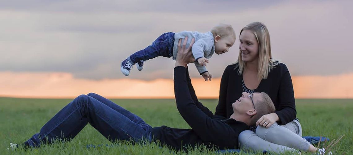 une famille dans les champs au soleil couchant